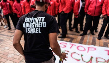 A pro-Palestinian activist spray-paints a banner in front of security officers during Israeli Apartheid Week at Witwatersrand University in Johannesburg, South Africa, March 7, 2017.