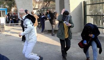 Iranian students run for cover from tear gas at the University of Tehran during a demonstration driven by economic problems, Tehran, Iran, December 30, 2017.