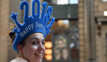 A woman sells 'Happy New Year 2018' headgear at Martin Place in Sydney, Australia, December 30, 2017.