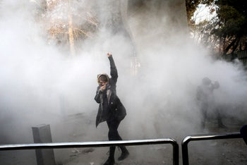 A university student attending a protest inside Tehran University while a smoke grenade is thrown by anti-riot Iranian police, Iran, December 30, 2017.