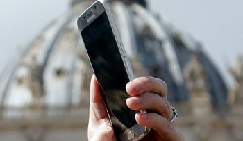A woman takes a picture with her mobile phone during the Angelus prayer delivered by Pope Francis in St. Peter's Square at the Vatican, Sunday, March 5, 2017.