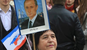 Woman holds a placard with a portrait of Russian President Vladimir Putin as she takes part in celebrations for the third anniversary of Russia's annexation of Crimea, in Simferopol, Crimea, March 16, 2017.