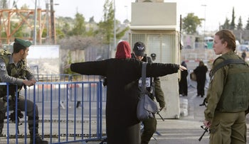 Security forces check a Palestinian woman at an East Jerusalem checkpoint in June 2016.