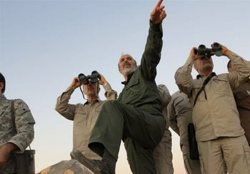 Iran's army chief of staff, Maj. Gen. Mohammad Bagheri, left, looking into binoculars as he visits a front line in the northern province of Aleppo, Syria, October 2017.