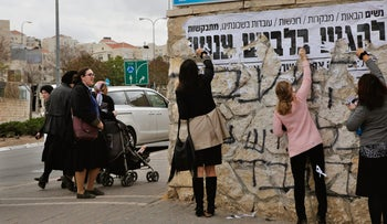 Women tearing down a banner calling for modest dressing in the central Israeli city of Beit Shemesh, December 2017.