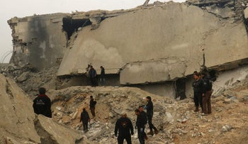 People inspect a damaged mosque after an airstrike on Jeeneh, in the Aleppo province, northwest Syria, March 17, 2017.