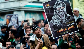 Supporters of the Fatah movement hold up a portrait of late Palestinian leader Yasser Arafat during a rally in Gaza City, December 31, 2017.