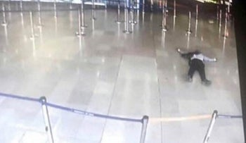 A picture taken of a television screen on March 18, 2017 shows a man lying on the ground at Paris' Orly airport after he was shot by French security forces for taking a weapon from a soldier.