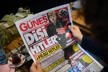 """A man reads an issue of Gunes, a Turkish pro-government daily newspaper, with on its front page German Chancellor Angela Merkel depicted in Nazi uniform with a Hitler-style moustache, labelling the German leader """"She Hitler"""", on March 17, 2017 in Istanbul, Turkey."""