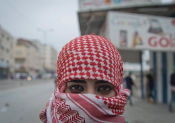 A female Palestinian protester covers her face during clashes with Israeli troops following protests against U.S. President Donald Trump's decision to recognize Jerusalem as the capital of Israel, at the outskirts of the West Bank city of Ramallah, Wednesday, Dec. 20, 2017.