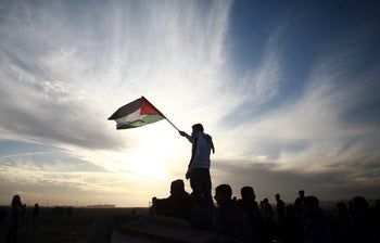 A Palestinian protester waves a national flag during clashes on the Israeli border with Gaza, Monday, Dec. 11, 2017.