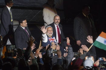 Narendra Modi, India's prime minister, center, waves to the crowd after speaking at a community reception in his honor at Wembley Stadium in London, U.K., on Friday, Nov. 13, 2015. British and Indian companies agreed on 9 billion pounds ($13 billion) of deals as Modi became the first Indian prime minister to visit the U.K. in almost a decade.