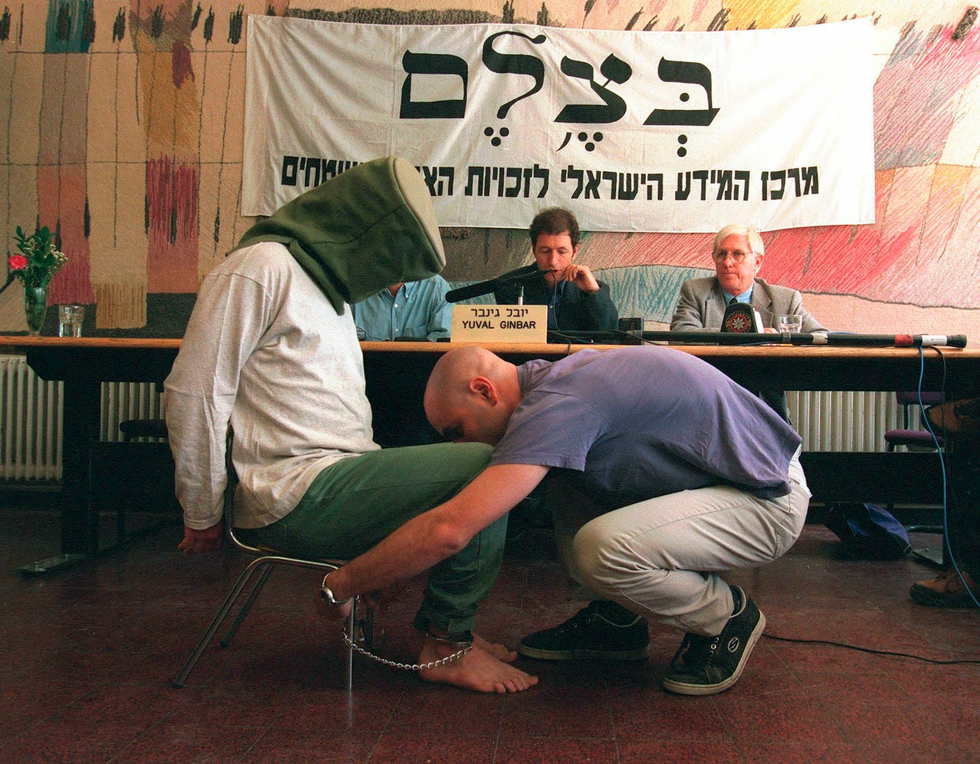 """An actor demonstrates the """"shabah"""" method, a torture method reportedly used by the Shin Bet during interrogations of Palestinians, at a B'Tselem press conference in Jerusalem, May 19, 1998."""