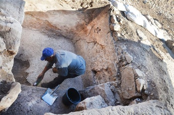 A laborer in the excavation cleaning a collecting vat of a winepress that was revealed at the site