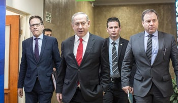 Prime Minister Benjamin Netanyahu heads to the weekly cabinet meeting, with Yoav Horowitz (R).