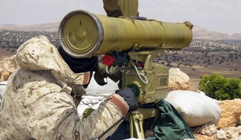A handout picture released by the Hezbollah press office on May 13, 2015, shows a Hezbollah fighter aiming his weapon on the Syrian side of the Qalamun hills close to the Lebanese borders.