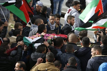 Palestinian mourners carry the body of Musab Firas al-Tamimi, 17, who was shot dead in clashes with the Israeli army, during his funeral in the village of Deir Nizam, West Bank, on January 4, 2018.