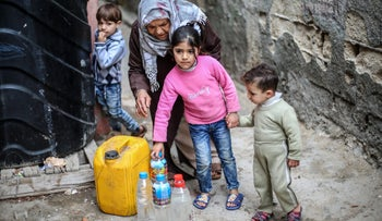 Palestinians filling bottles and jerrycans with drinking water at the Al-Shati refugee camp in the southern Gaza Strip. March 22, 2017