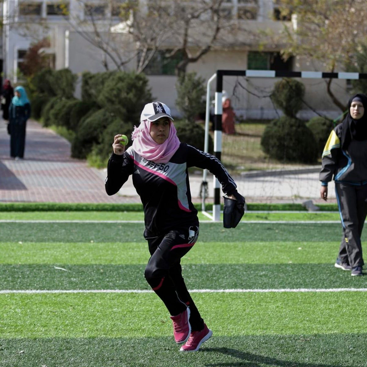 In this Sunday, March 19, 2017 photo, Palestinian women train for an all women's baseball game, on a soccer field, in Khan Younis, southern Gaza Strip. The female players wear hijabs, not helmets, toss around tennis balls, not baseballs and their leather gloves have been replaced by black imitations knitted from fabric. The group of young women are trying to bring baseball to Gaza -- giving the traditional American pastime a distinctly local feel.