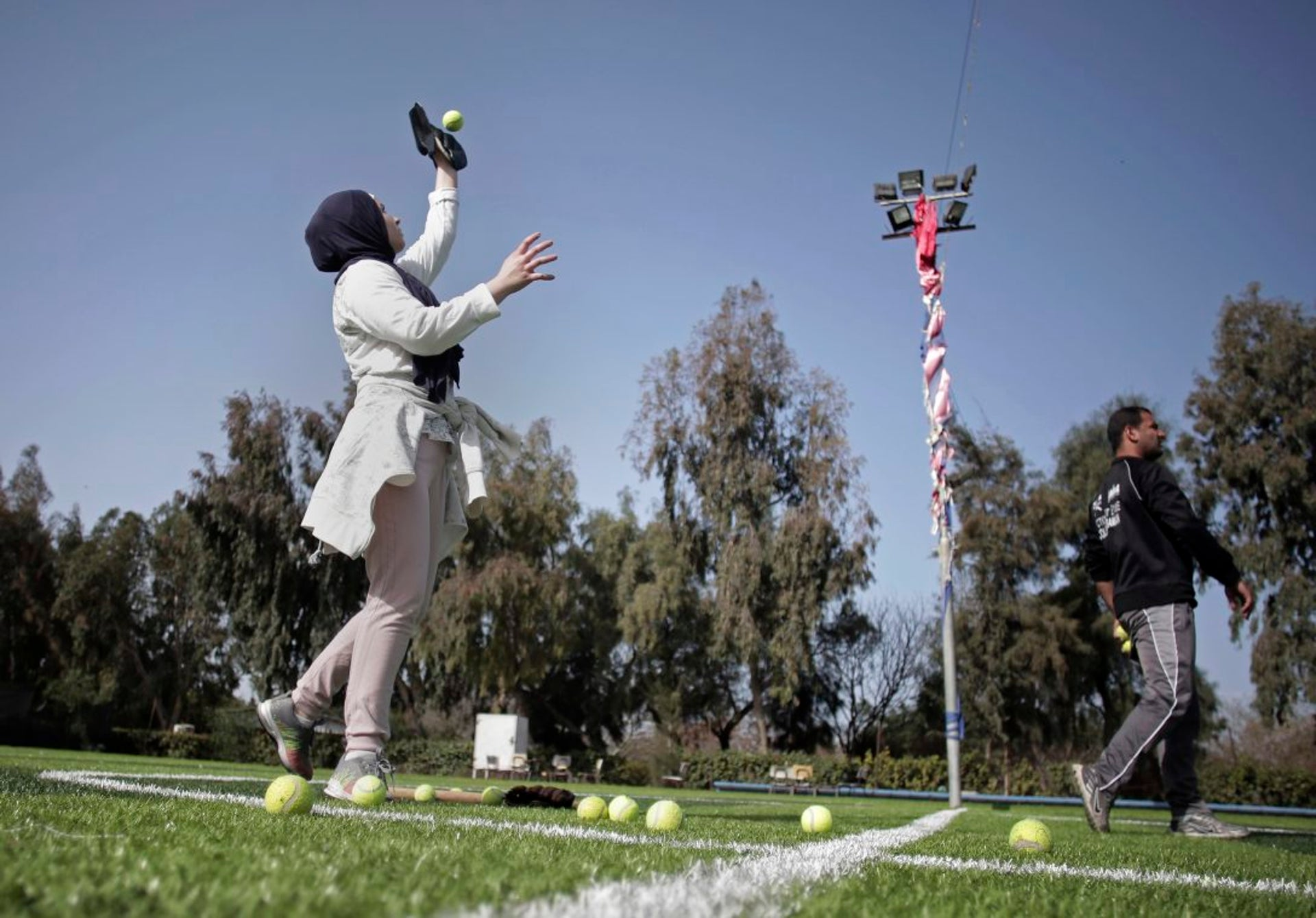 In this Sunday, March 19, 2017 photo, Palestinian women train for an all women's baseball game, on a soccer field in Khan Younis, southern Gaza Strip. The female players wear hijabs, not helmets, toss around tennis balls, not baseballs and their leather gloves have been replaced by black imitations knitted from fabric. The group of young women are trying to bring baseball to Gaza -- giving the traditional American pastime a distinctly local feel.