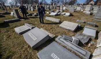 Northeast Philadelphia Police Detectives Nick McReynolds, left, and Thomas Walsh look over headstones that were vandalized at Mount Carmel Cemetery in Philadelphia on Sunday, Feb. 26, 2017.