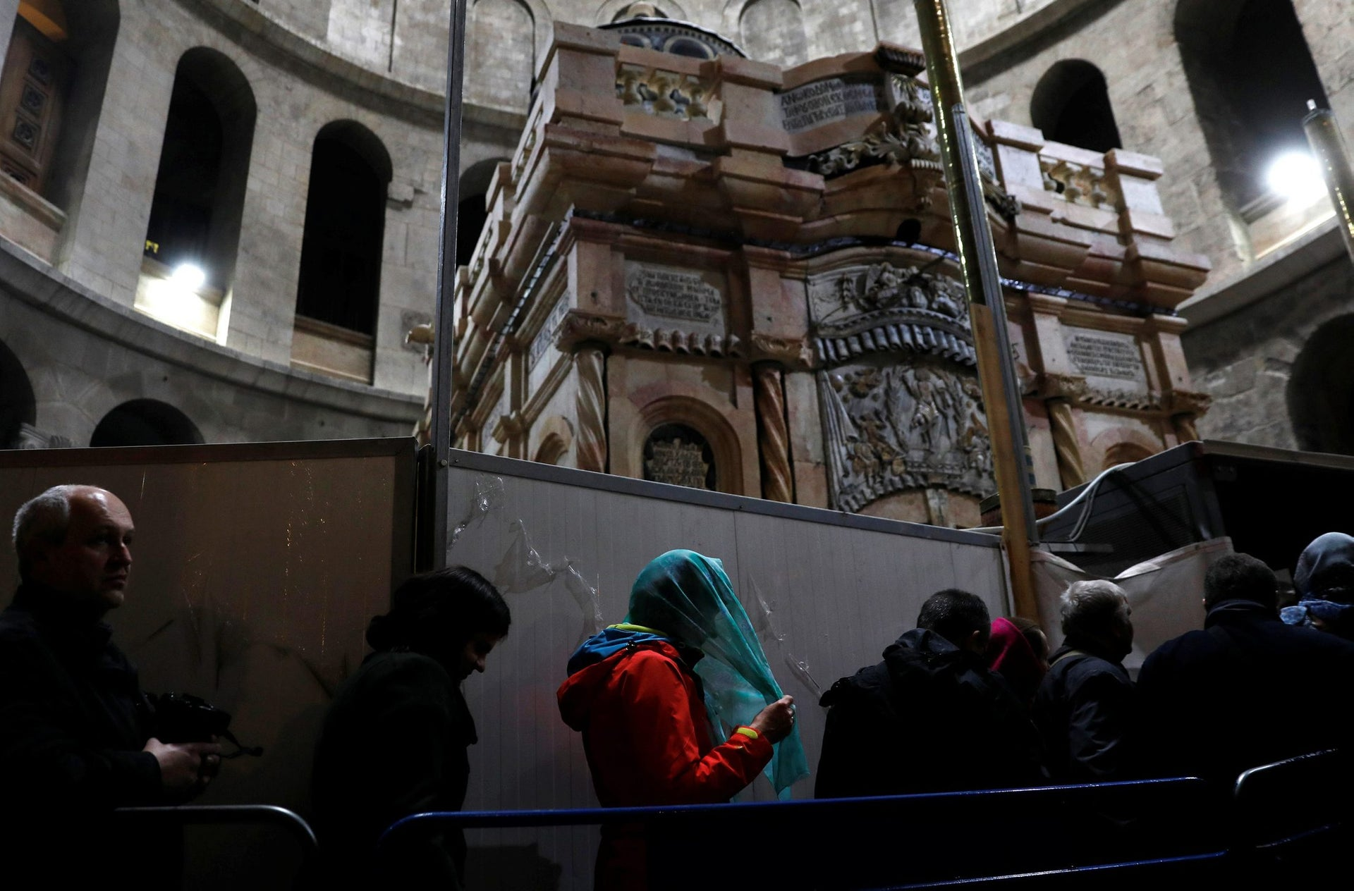 Visitors stand near the newly restored Edicule, the ancient structure housing the tomb, which according to Christian belief is where Jesus's body was anointed and buried, at the Church of the Holy Sepulchre in Jerusalem's Old City March 20, 2017.