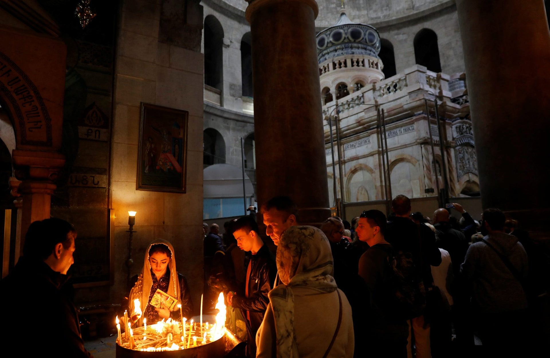 Worshippers light candles as the newly restored Edicule, the ancient structure housing the tomb, which according to Christian belief is where Jesus's body was anointed and buried, is seen in the background at the Church of the Holy Sepulchre in Jerusalem's Old City March 20, 2017.