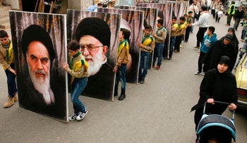 Young supporters of Hezbollah carry portraits of Iran's Ayatollah Khomeini and Ayatollah Khamenei in the southern Lebanese town of Kfar Hatta, March 18, 2017.
