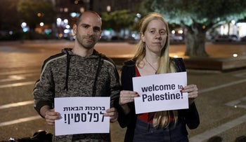 """Activists Ronnie Barkan and Lihi Rothschild hold signs that read, """"Welcome to Palestine"""" in Tel Aviv, 2012."""