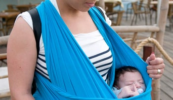 A mother holding her infant in a baby carrier.