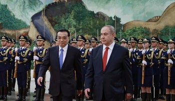 Prime Minister Benjamin Netanyahu walks with Chinese Premier Li Keqiang during a welcome ceremony in Beijing, March 20, 2017.
