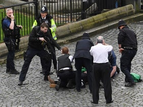 A policeman points a gun at a man on the floor as emergency services attend the scene outside the Palace of Westminster, London, Wednesday, March 22, 2017.