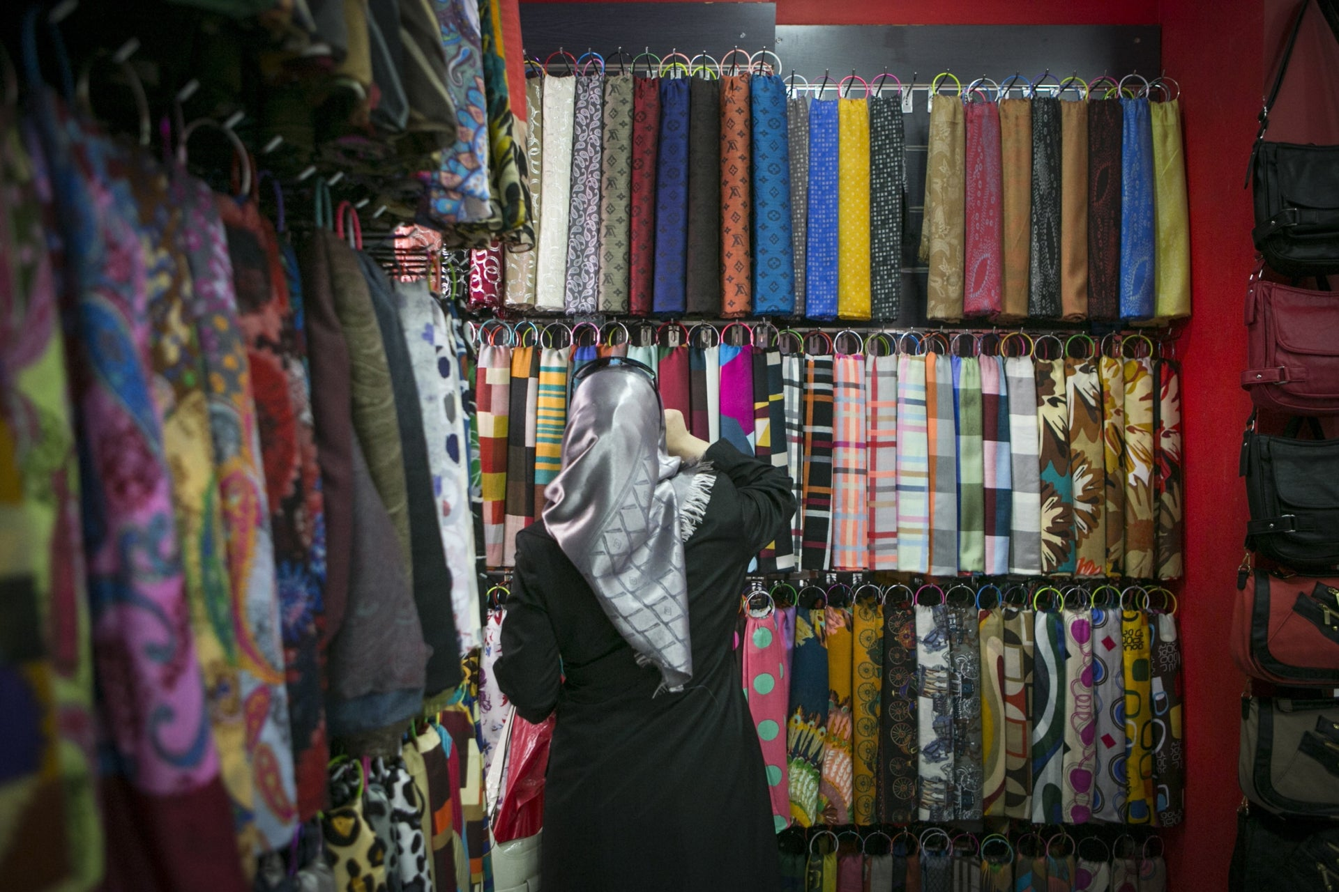 A woman browsing through rows of hijabs at a store in Ramallah.
