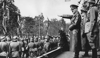 In this March 1938 file photo, Adolf Hitler salutes German troops parading in Vienna, Austria.