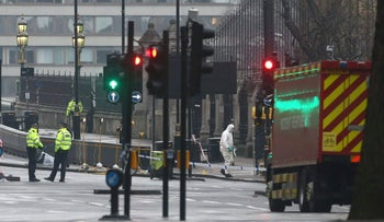 Forensics investigators and police officers work at the site of Wednesday's attack near the British Parliament in London, March 23, 2017.