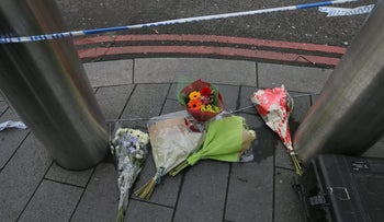 Flower tributes left on pavement on the edge of a police cordon near parliament in London, March 23, 2017