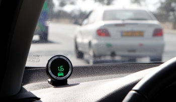 A device, part of the Mobileye driving assist system, seen on the dashboard of a vehicle.
