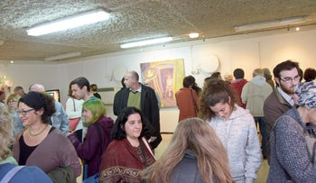 Attendees viewing art at the Mimosa Hour exhibition in Modi'in.