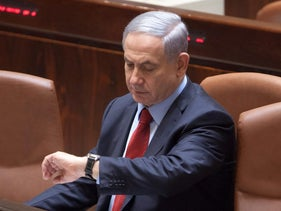 Prime Minister Benjamin Netanyahu looks at his watch in the Knesset.