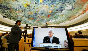Palestinian President Mahmud Abbas is seen on a TV screen while speaking during a meeting of the United Nations Human Rights Council on February 27, 2017 in Geneva, Switzerland.