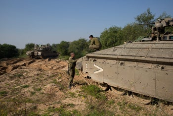 An Israeli soldier sits on top of a tank on the Israeli border with the northern Gaza Strip near the southern Israeli village of Netiv Haasara on January 13, 2016.
