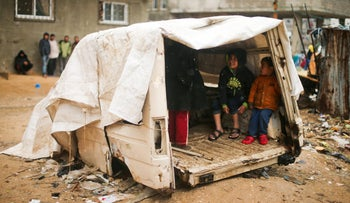 Children in Gaza taking shelter in the remains of a vehicle during a rainstorm, February 2017.