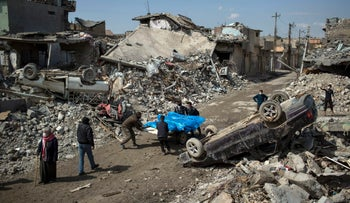 Residents carry the bodies of several people killed during clashes between Iraqi security forces and ISIS in Mosul, Iraq, March 24, 2017.