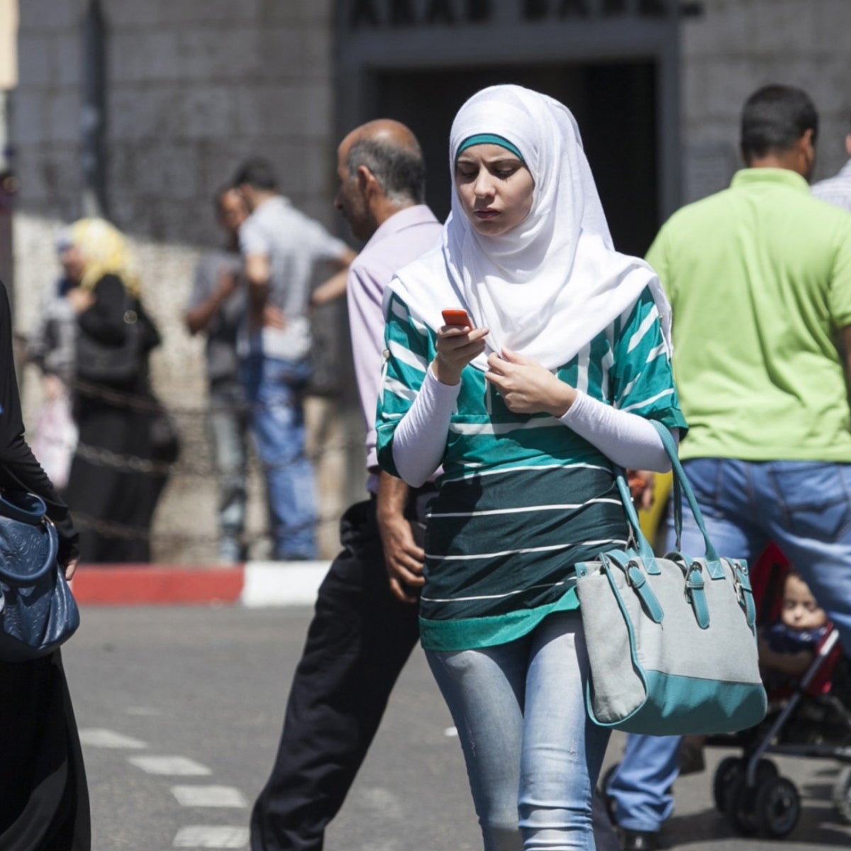 A woman in Ramallah wearing Western-style clothing and a hijab.