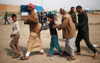 Displaced residents who fled their homes move to be searched by Iraqi troops, in western Mosul, Iraq March 28, 2017.