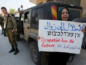 FILE PHOTO: A Palestinian woman holds a sign near Israeli forces during a protest against Jewish settlements in the West Bank city of Hebron March 26, 2017.