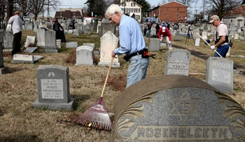 File photo: Volunteers clean up debris at Mount Carmel Cemetery in Philadelphia. Feb. 28, 2017.