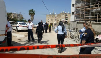 The murder scene in Tiberias, March 29, 2017. Police officers inspect a sidewalk area sealed off with red police tape.