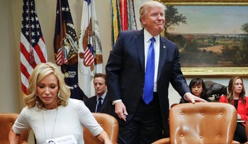 President Donald Trump takes his seat next to National Rifle Associations (NRA) Executive Vice President and Chief Executive Officer Wayne LaPierre, right, and Pastor Paula White of the New Destiny Christian Center. Feb. 1, 2017.