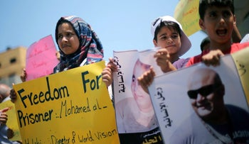 Palestinians protest in solidarity with Mohammad El Halabi, World Vision's manager of operations in Gaza who was accused by Israel of funnelling aid money to Hamas, in Gaza City August 7, 2016.